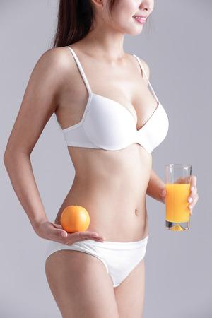 bikini slender: Beautiful slim body of woman and orange juice isolated on gray background Stock Photo