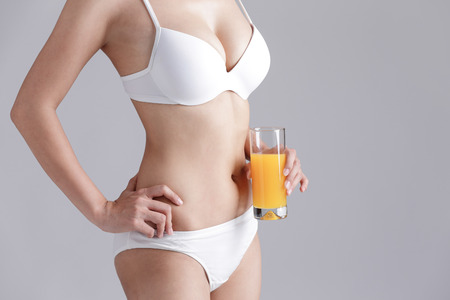 grijze achtergrond: Beautiful slim body of woman and orange juice isolated on gray background Stockfoto