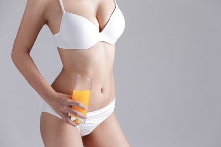 beautiful woman body: Beautiful slim body of woman and orange juice isolated on gray background Stock Photo