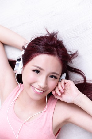 enjoy space: Young woman enjoying the music and relax lying at home, asian beauty