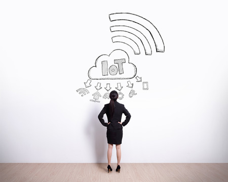 Back view of business woman look internet of things drawing on white wall background Stock Photo