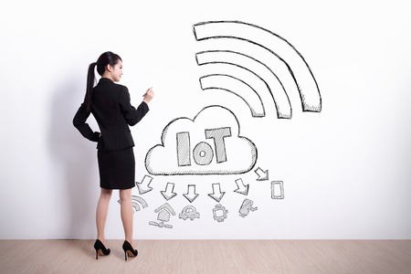 rear view girl: Back view of business woman writing internet of things on white wall background, asian