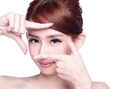 belleza: Cara de la mujer y el cuidado de los ojos y ella hace el marco con las manos, belleza asiática