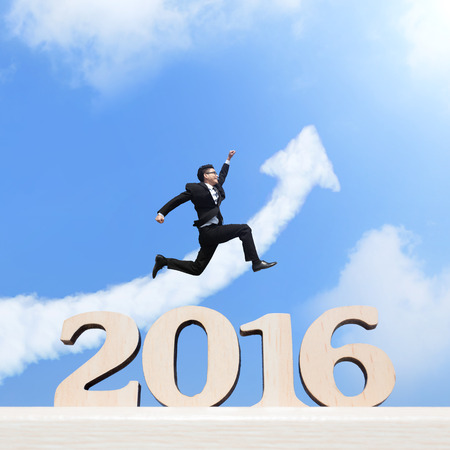 Happy new year for 2016 - success business man jump in the air cheering and celebrating on wood number