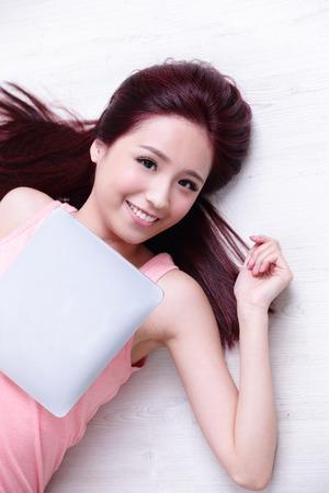 ojo humano: Hermosa mujer joven feliz relajarse tumbado y que usa la PC de la tableta digital, belleza asi�tica Foto de archivo