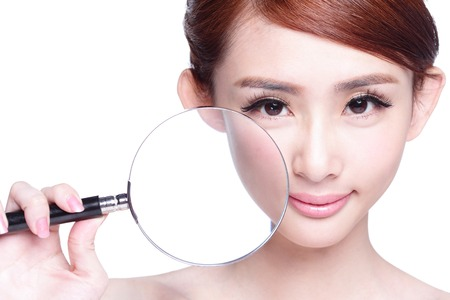 young woman with perfect skin and magnifying glass check it isolated, concept for skin care, asian