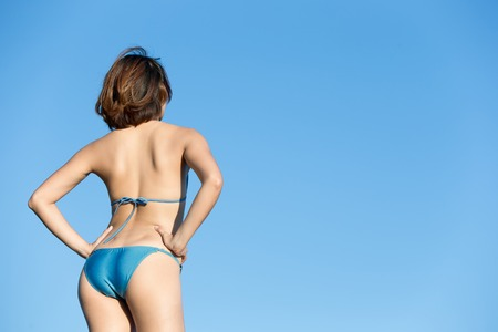 Back view of happy girl wear bikini at sea beach and look landscape, asian beauty