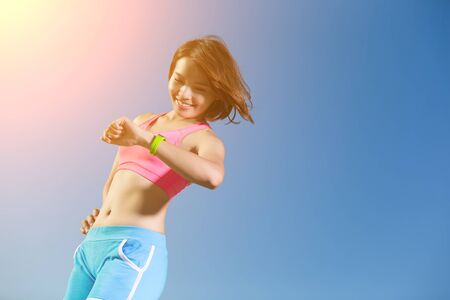 jog: Health sport woman wearing smart watch device with touchscreen doing exercises with blue sky, asian beauty Stock Photo