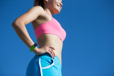 women sport: Health sport woman wearing smart watch device with touchscreen doing exercises with blue sky, asian beauty Stock Photo