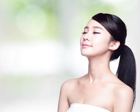vẻ đẹp: Xinh đẹp chăm sóc da phụ nữ khuôn mặt nụ cười vô tư và tận hưởng thiên nhiên bị cô lập trên nền màu xanh lá cây. Vẻ đẹp Châu Á