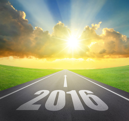 december sunrise: Forward to 2016 new year concept , asphalt road with arrow , date and beautiful sunset and sunshine Stock Photo