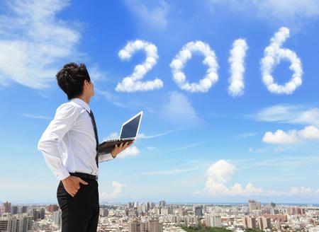 diciembre: Hombre de negocios joven usando la computadora portátil y buscar a 2.016 años de texto con el cielo azul y las nubes y el paisaje urbano en el fondo, asiático Foto de archivo