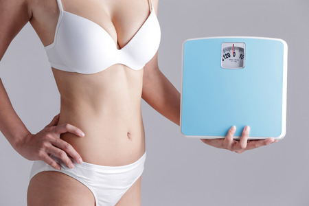slim tummy: Health and slim body of woman holding scale isolated on gray background
