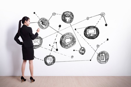 Back view of business woman writing internet of things on white wall background