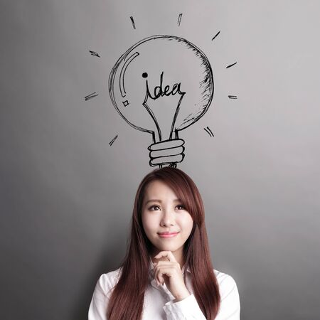 business idea: Thinking business woman and look idea lightbulb isolated on grey background Stock Photo