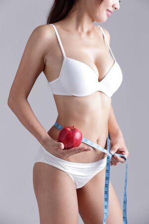 cintura: Ajustar la mujer está el cuerpo de medición aislada en el fondo gris Foto de archivo