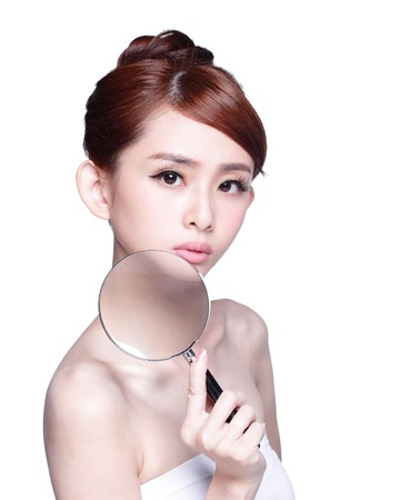female model: young woman with perfect skin and magnifying glass isolated Stock Photo