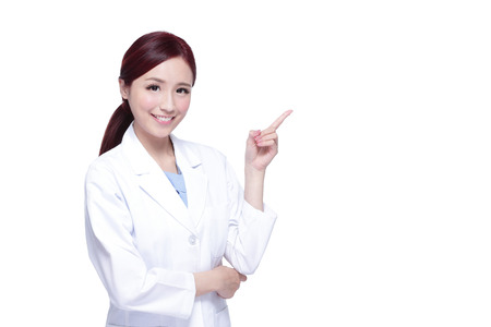 Smiling medical doctor woman show something. Isolated over white background Stock Photo