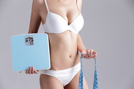 bikini slender: Health and slim body of woman holding scale isolated on gray background