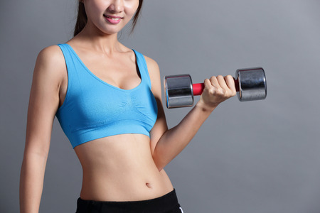 asian bodybuilder: Sport woman is lifting weights isolated on the grey background