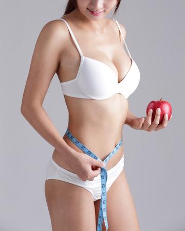ropa interior niñas: Ajustar la mujer está el cuerpo de medición aislada en el fondo gris Foto de archivo