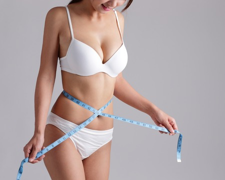 scales thin: Woman measuring shape of beautiful waist for Healthy lifestyles concept with gray background Stock Photo