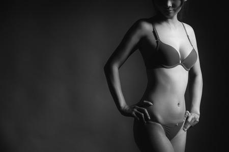 hot breast: Привлекательная секси женщина с красивое тело, создавая и носить нижнее белье в монохромном черные и белые тона Фото со стока