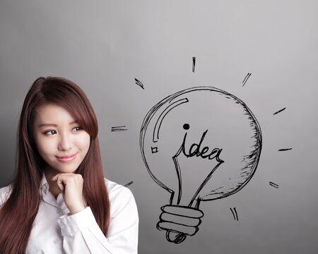 Denken zakelijke vrouw en kijken naar idee gloeilamp geïsoleerd op een grijze achtergrond
