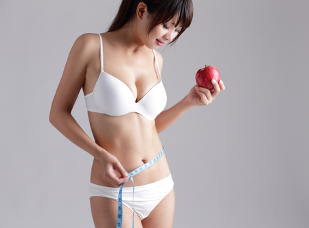 sexy asian girl: Fit woman is measuring body and hold apple isolated on the background, asian Stock Photo