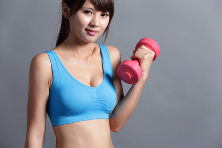 female muscle: Sport woman is lifting weights isolated on the background, asian. Stock Photo