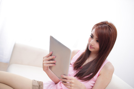 using tablet: happy woman using tablet pc on sofa in the living room, asian beauty