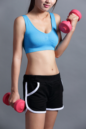 female fitness: Sport woman is lifting weights isolated on the background, asian. Stock Photo