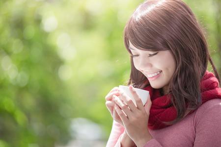 freddo: sorridere giovane donna con una tazza di caffè o tè e indossa abiti invernali con sfondo verde, asiatico bellezza