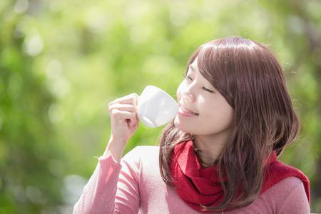 hot asian: улыбаться молодая женщина, держащая чашку кофе или чая и носить зимнюю одежду с зеленым фоном, азиатской красоты