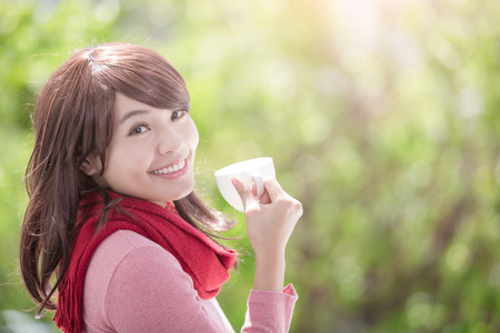 winter weather: smile young woman holding cup of coffee or tea and wearing winter clothing with green background, asian beauty Stock Photo