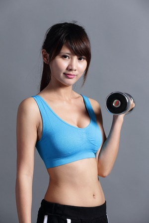 sexy asian girl: Sport woman is lifting weights isolated on the background, asian. Stock Photo