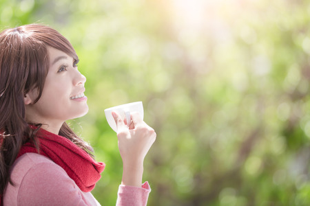 smile young woman holding cup of coffee or tea and wearing winter clothing with green background, asian beauty Archivio Fotografico