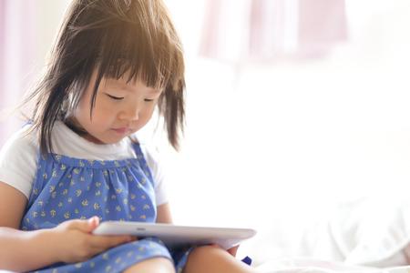 play: Chica niño juego de play feliz con tablet PC. Niño asiático
