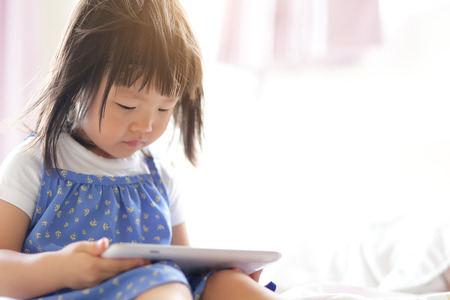 touch technology: child girl happy play game with tablet PC. asian child Stock Photo