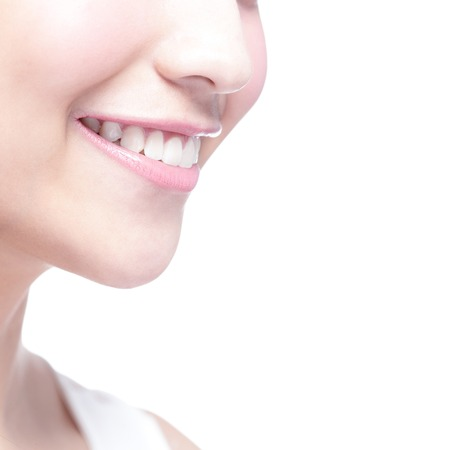 close  up: Beautiful young woman health teeth close up and charming smile. Isolated over white background, asian beauty