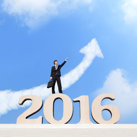 year increase: Happy new year for 2016 - Successful business man purposefully looking away and celebrating on wood number