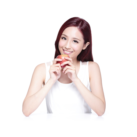woman eat: Beauty woman with Apple and charming smile to you, she rests her elbows on white table, asian beauty Stock Photo