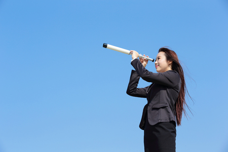 business concepts: Business woman with telescope ( spyglass ) looking forward Prospects for future business with blue sky background, asian beauty