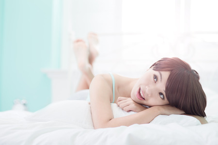 wellness sleepy: Charming woman Smile face close up and she lying on the bed in the morning , asian girl Stock Photo
