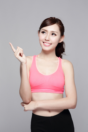 Sport girl look something isolated on grey background. asian beauty