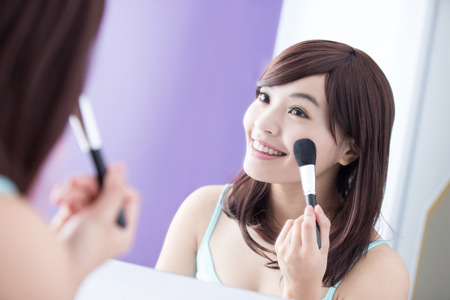 asian girl face: Close up of Smile woman with makeup brushes near face and look mirror. asian beauty Stock Photo