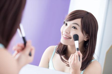 Gros plan de sourire femme avec pinceaux de maquillage près de visage et regard miroir. asiatique beauté