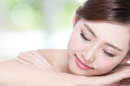 body care: Charming woman face Smile enjoy spa and massage while lying with green background, asian girl