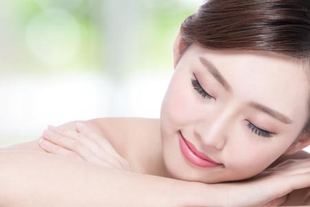 piel: Rostro de mujer encantadora sonrisa disfrutar de spa y masajes mientras está acostado con el fondo verde, muchacha asiática Foto de archivo