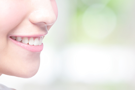 a close up: Beautiful young woman health teeth close up and charming smile. with green background, asian beauty Stock Photo